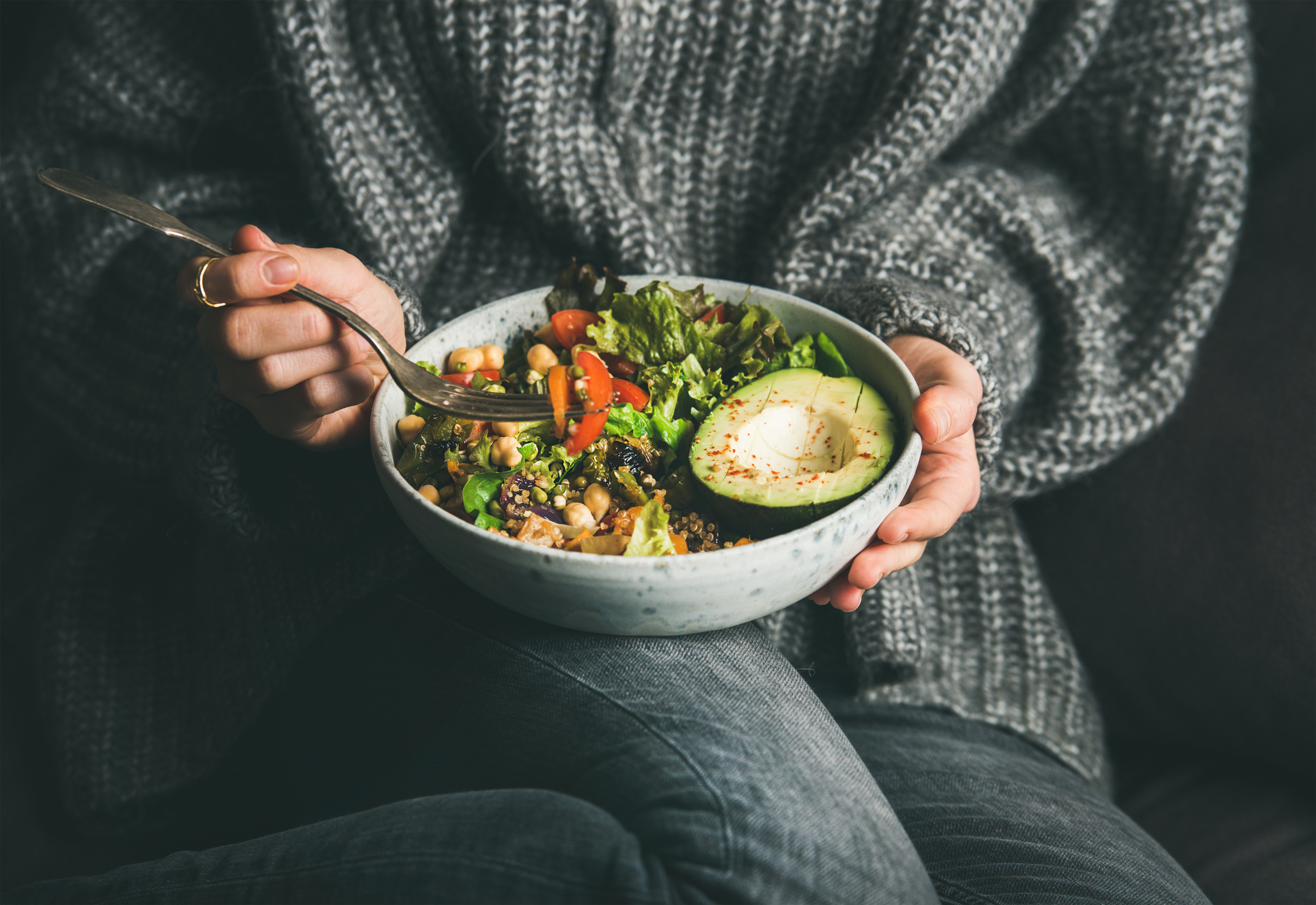 Woman in sweater eating fresh salad with macros and micros