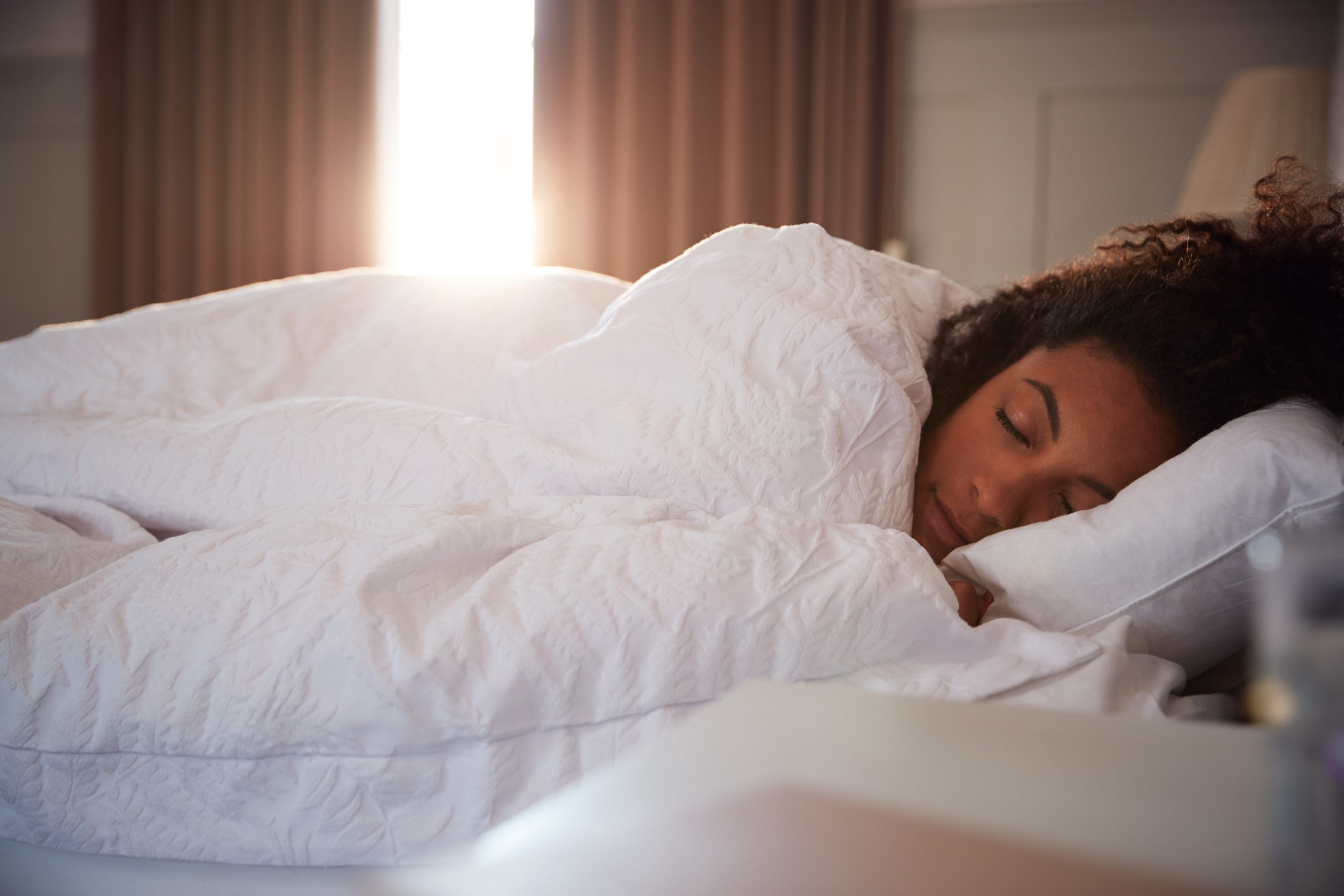 Peaceful woman sleeping in bed in duvet cover