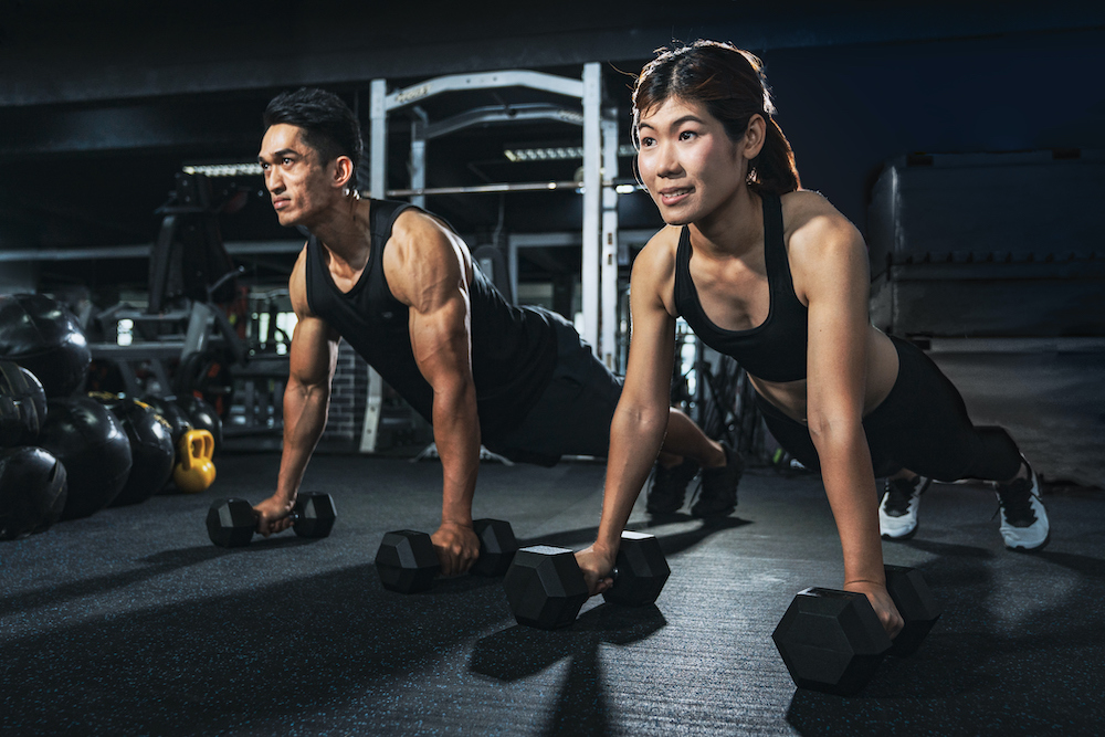 Young couple lifting weights at gym
