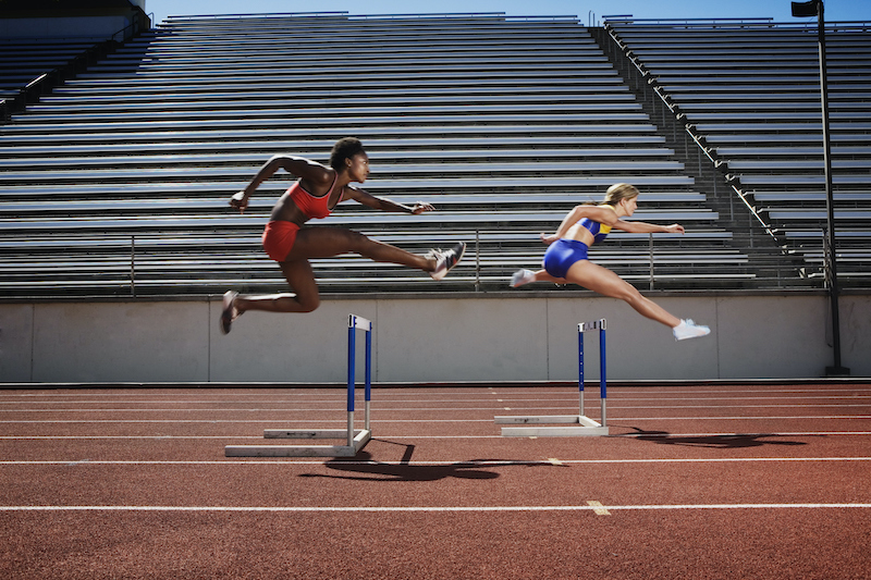 Two women jumping in a racing track at the Olympics