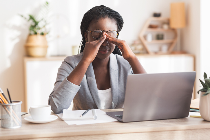 A stressed worker sitting at her desk