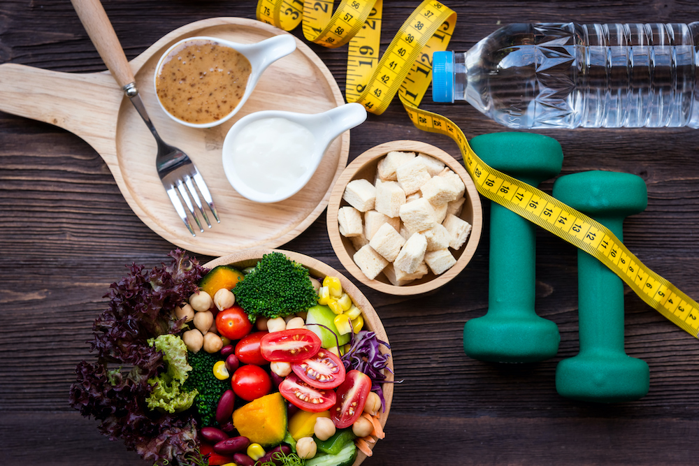 Fresh salad, water and weights to keep health