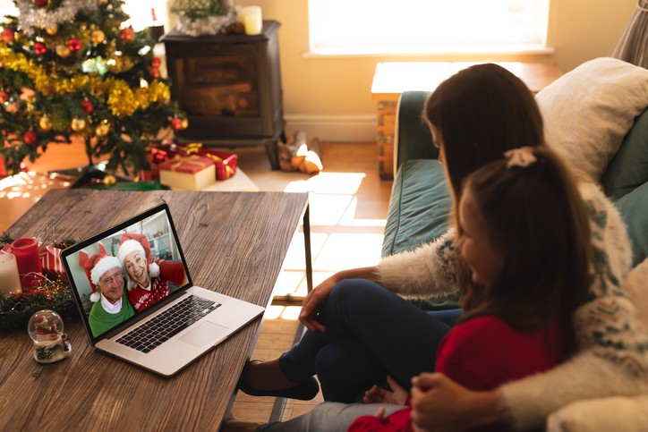 Woman and daughter sitting on couch having a videocall with senior couple in santa hats smiling