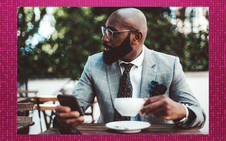 Man sitting at table with his phone and a mug