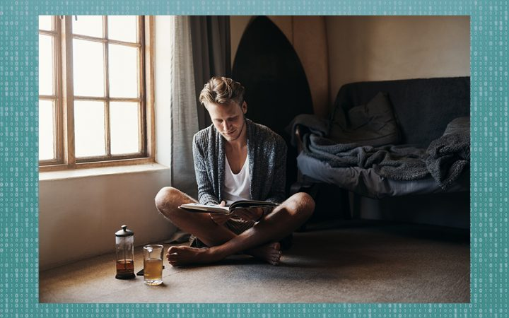 Man sitting on the floor reading a book