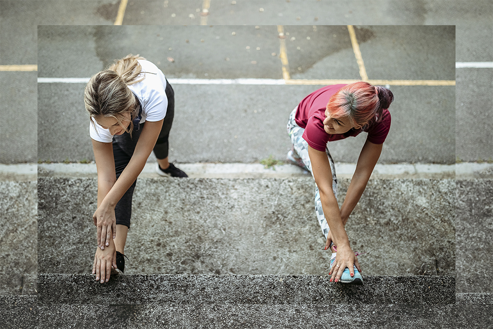 Image of two women warm up stretching