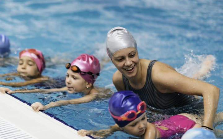 Children and woman practicing swimming routine strokes at the wall