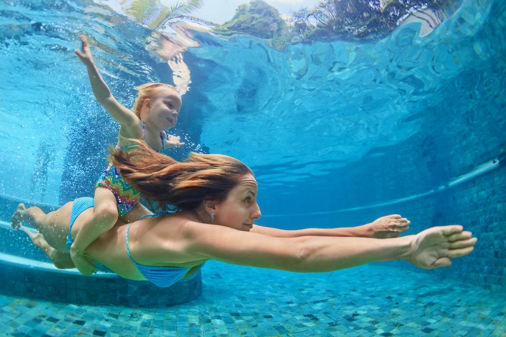 Mum and daughter swimming in pool