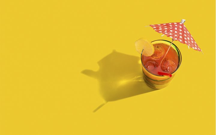 Cocktail on yellow background for cutting. alcohol to help with IBS
