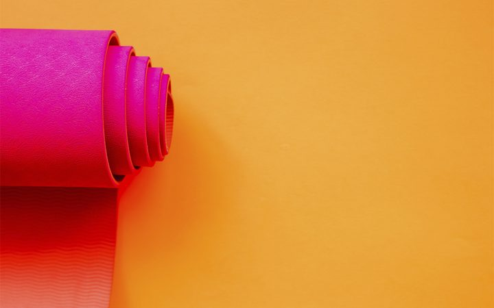Pink yoga mat rolled up on orange background