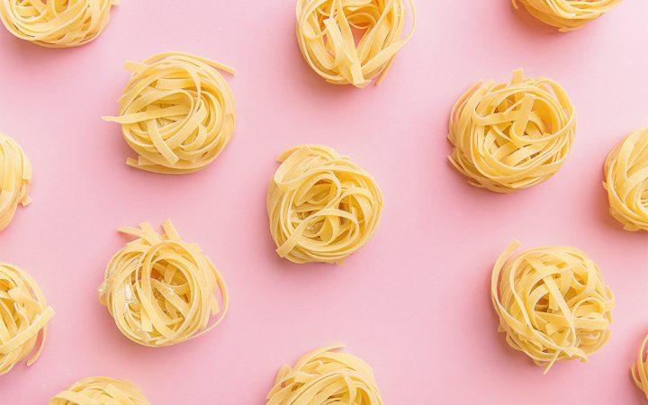 Spiralled pasta on baby pink background
