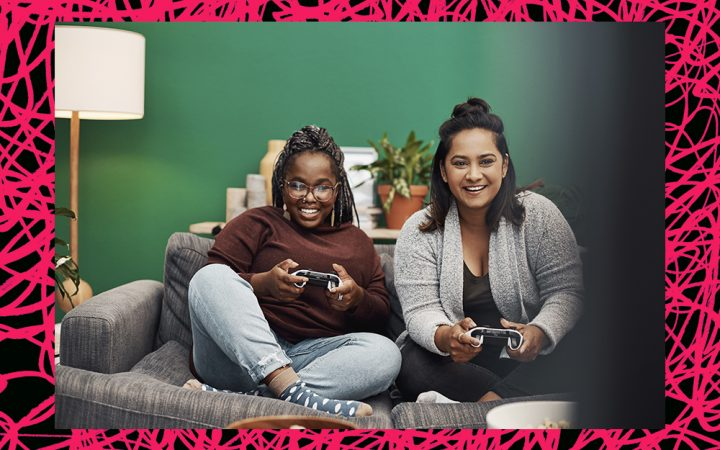 two female friends playing games and having fun together at home instead of having social burnout