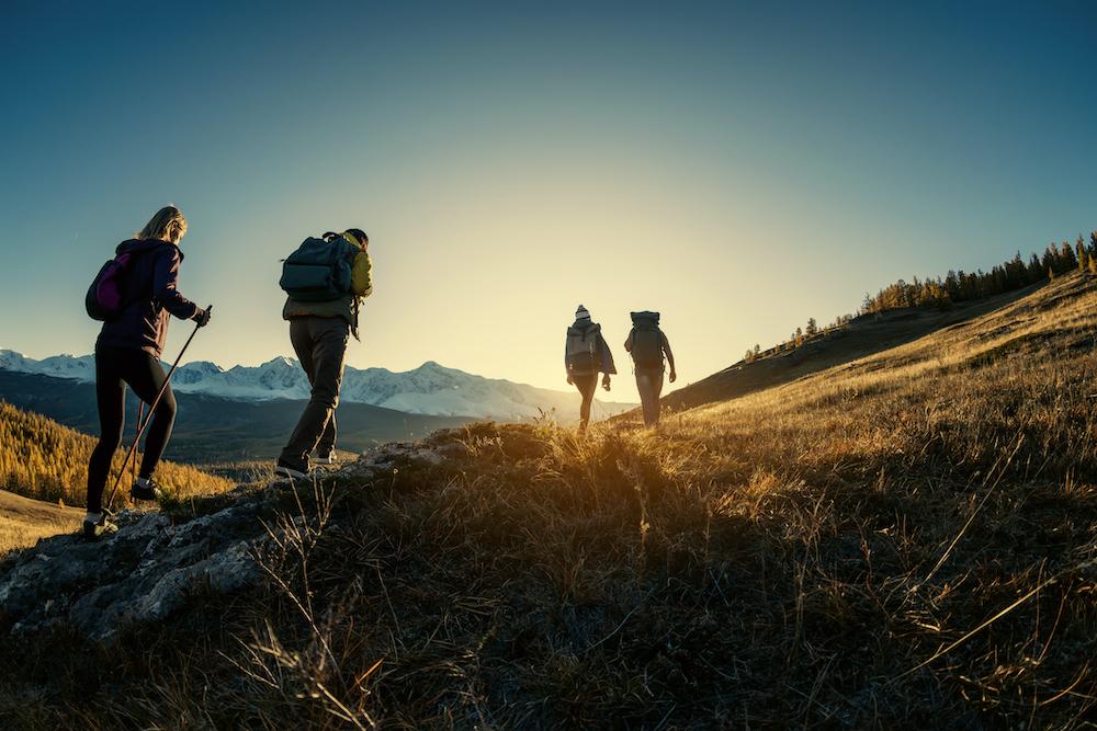 Four people walking at sunset