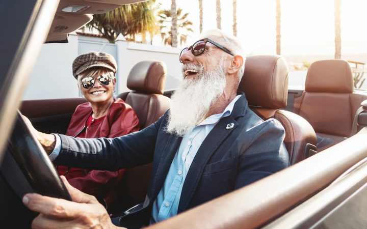 Older couple driving and laughing
