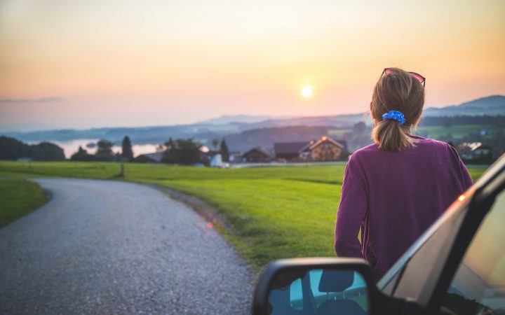 Woman sat on car staring into sunset in countryside