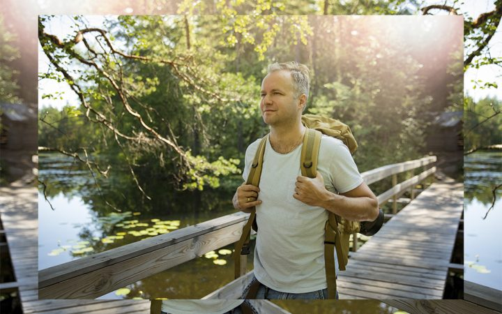 Man walking through the woods practicing soundwalking