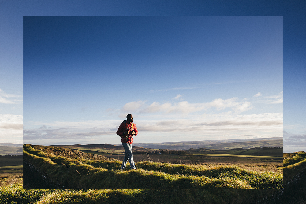 Man walking througyh countryside in jacket in sunshine