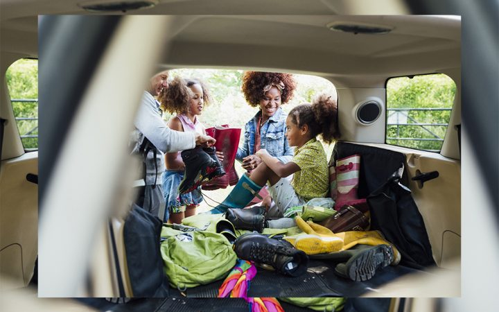 Family packing their vehicle boot to get ready for a car trip