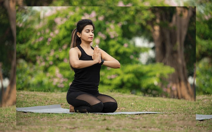 Woman outside in nature practicing yoga