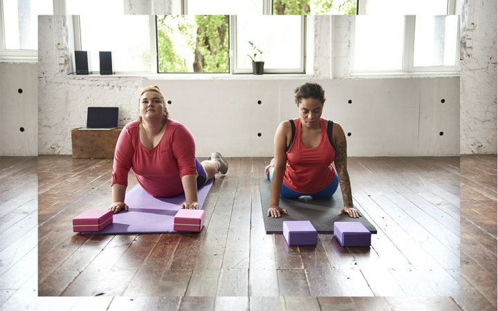Two women in living doing stretches