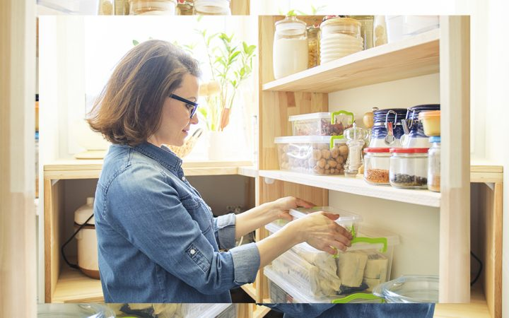 Woman in kitchen getting rid of cling film to be more sustainable