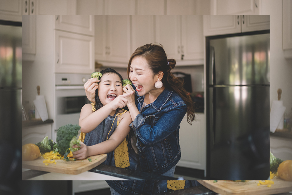 Mother and daughter in kitchen laughing with sustainable vegetable brocoli