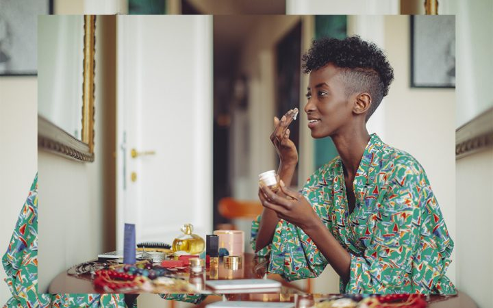 Black woman applying cream to her face at home