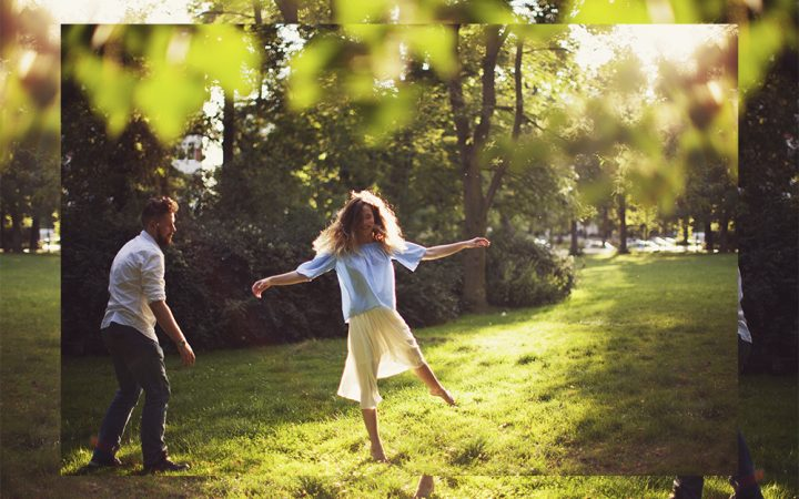 Man and woman couple outside laughing and dancing