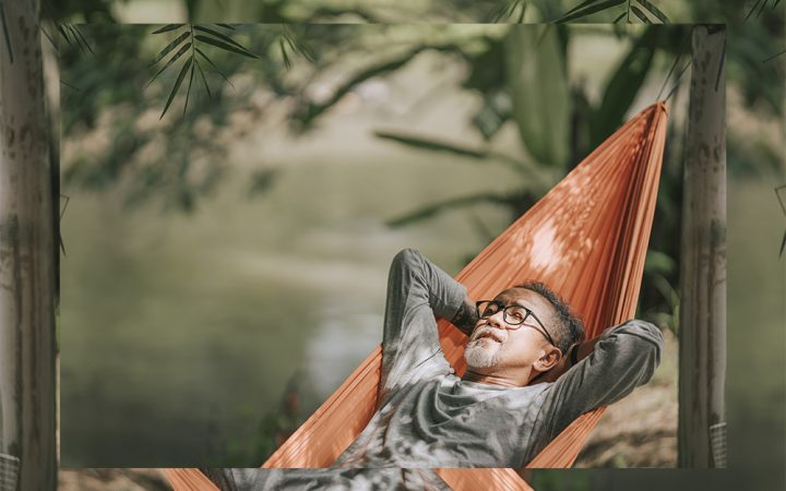 Black man in hammock laying and relaxing in the sun