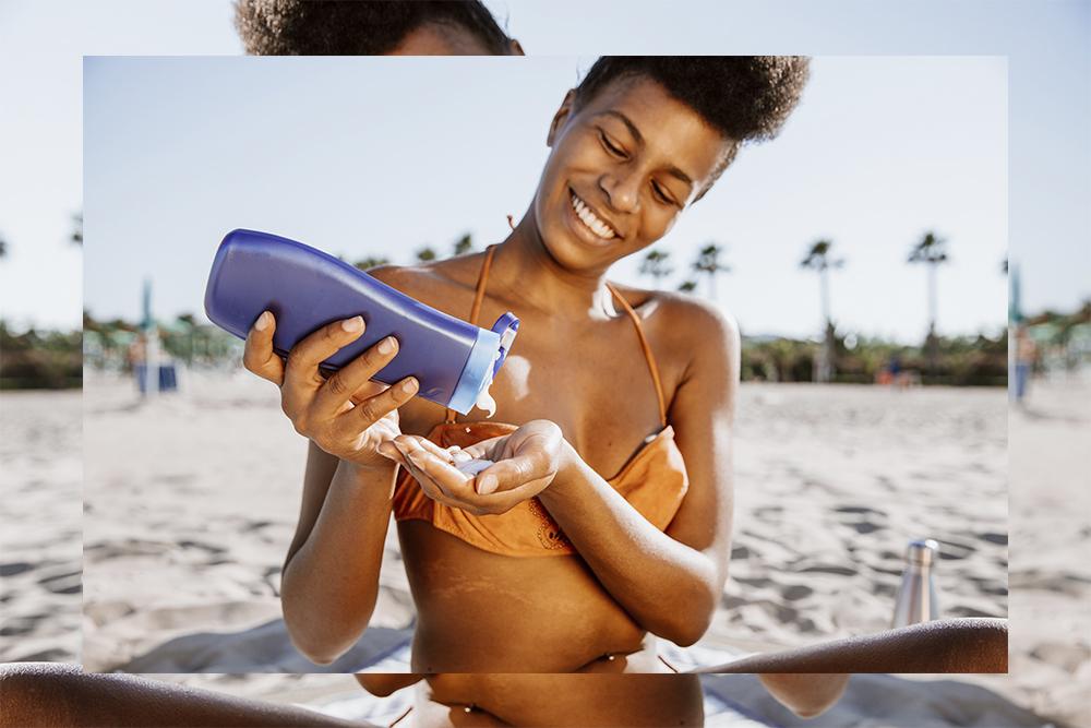 Black woman applying sun lotion