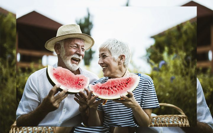 Older couple eating watermelon and laughing