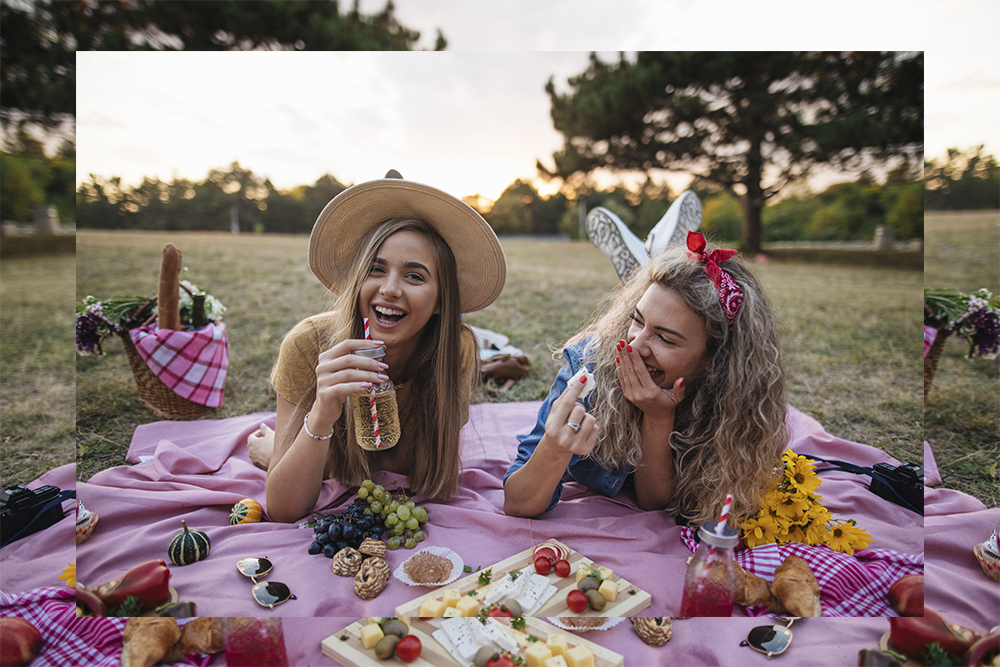 Two friends in the park having a picnic