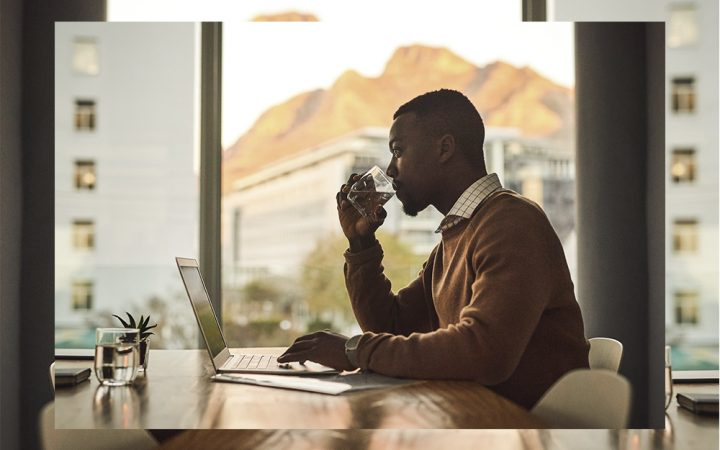 Man drinking water at desk